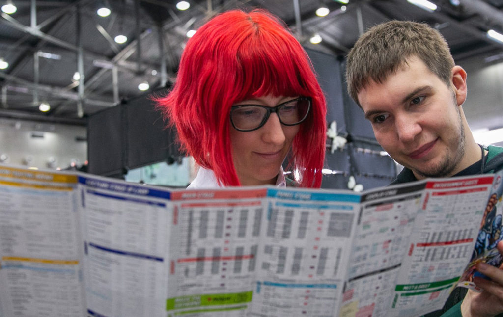 An image of two Vienna Comic Con visitors looking at a map of the event